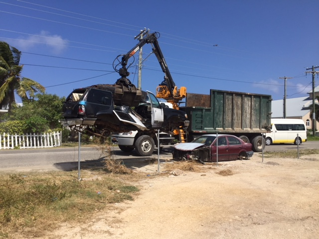 DEH's grabber truck lifts one of the final two derelict cars