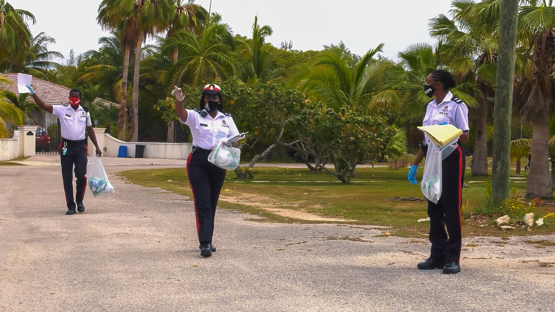 Three members of the RCIPS Community Department team hands out reusable cloth masks and flyers in a West Bay Road neighbourhood.