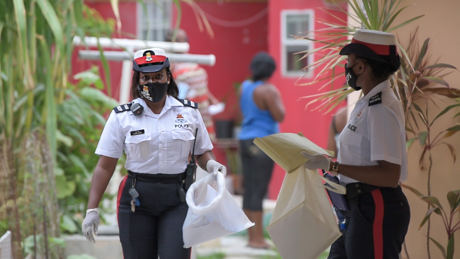 Two RCIPS officers distributing masks in a George Town community.